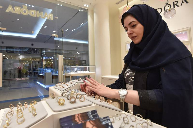 """Saudi Rodina Maamoun, who employed 19 young women almost entirely replacing the men, sells jewellery at a retail store in Riyadh's Hayat mall on February 19, 2020. - For decades, straitlaced Saudi society offered limited opportunities for paid work to women. The few who found jobs were mostly restricted to the health and education sectors. An oppressive """"guardianship"""" system also gave male relatives the right to object to women' professional aspirations. But change came in mid-2016 when Crown Prince Mohammed bin Salman unveiled his """"Vision 2030"""" plan aimed at diversifying the kingdom's economy and ending its addiction to oil. (Photo by FAYEZ NURELDINE / AFP)"""