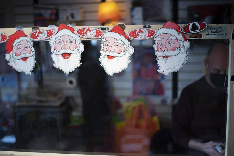 REHOBOTH BEACH, DE - NOVEMBER 27: A string of Santa Claus decorations hang from a plexiglass divider to separate a cashier and customers during Black Friday on November 27, 2020 in Rehoboth Beach, Delaware. Due to the coronavirus (COVID-19) pandemic, face masks are required on the boardwalk and strongly recommended on the beach.   Mark Makela/Getty Images/AFP == FOR NEWSPAPERS, INTERNET, TELCOS & TELEVISION USE ONLY ==
