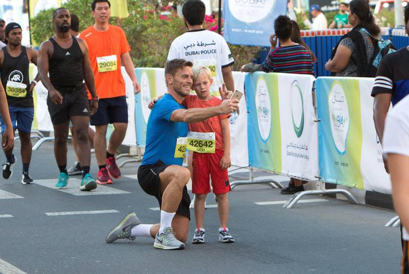 Dubai, United Arab Emirates - Participants father and son doing selfie at the finish line at the Dubai 30x30 Run at Sheikh Zayed Road.  Leslie Pableo for The National