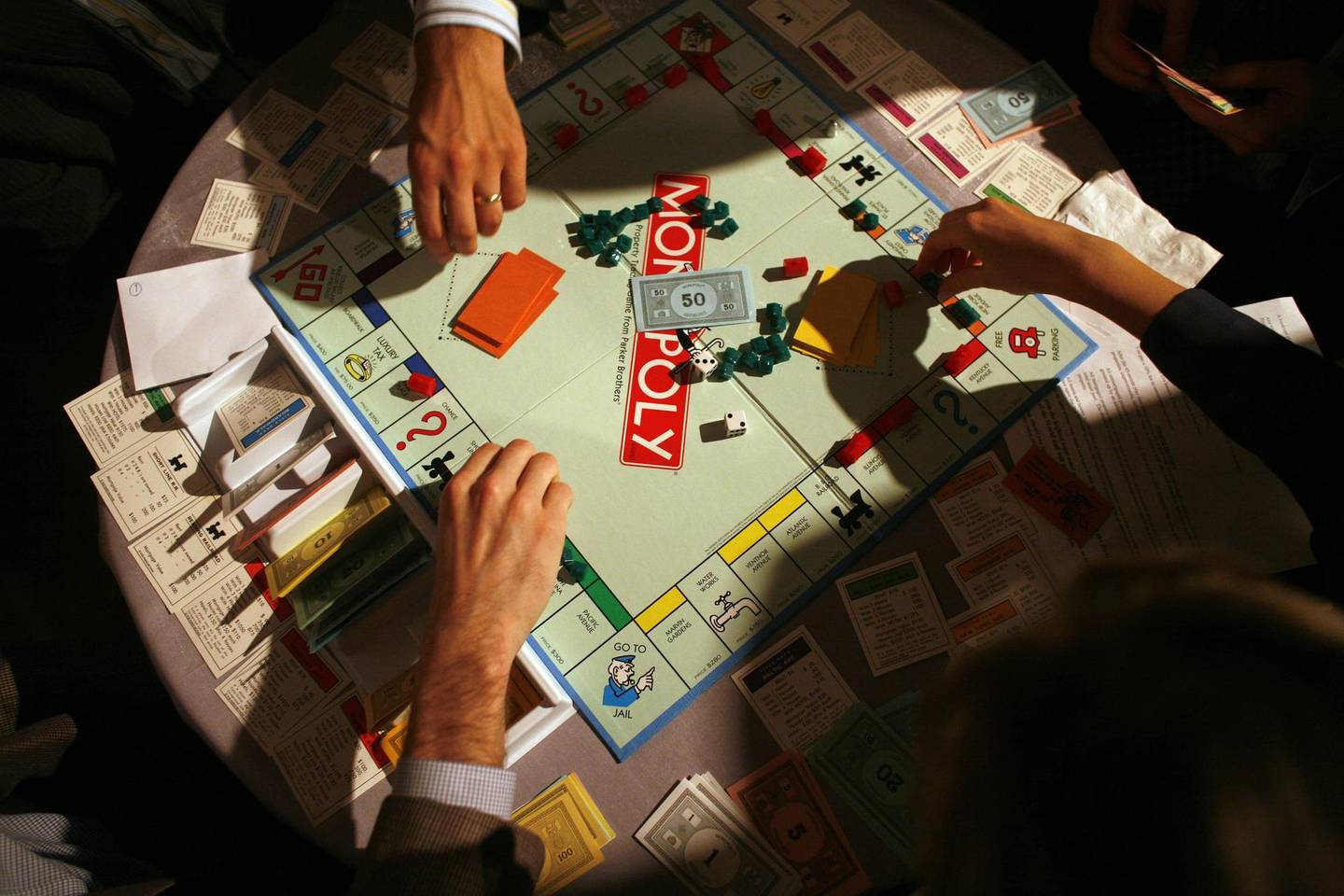 People move game pieces on the board game Monopoly, manufactured by Hasbro Inc., at the New York University Real Estate Institute Monopoly event on Tuesday, November 14, 2006. Photographer: Michael Nagle/Bloomberg News.