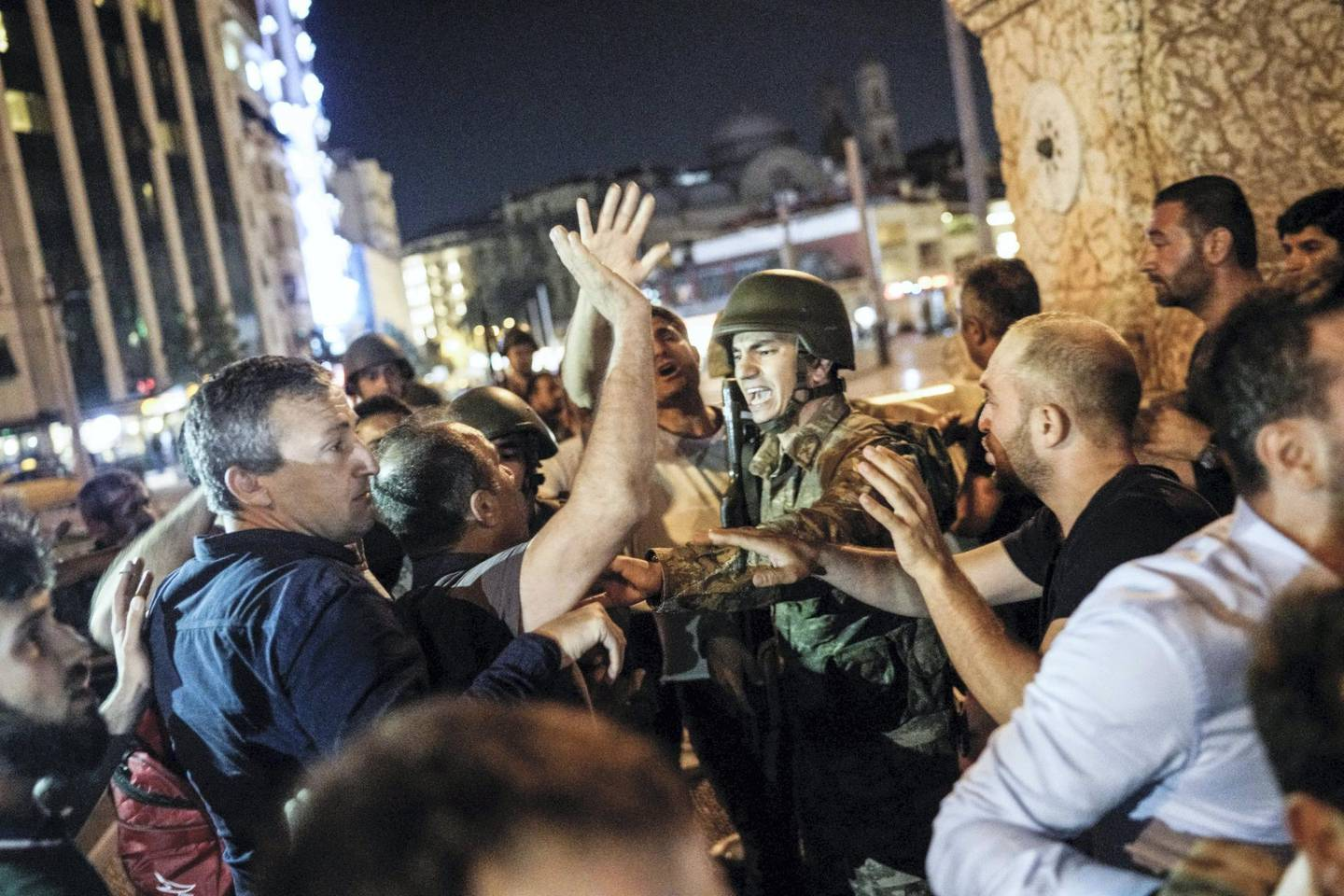 People react towards a Turkish solder at Taksim square in Istanbul on July 16, 2016.  Turkish military forces on July 16 opened fire on crowds gathered in Istanbul following a coup attempt, causing casualties, an AFP photographer said. The soldiers opened fire on grounds around the first bridge across the Bosphorus dividing Europe and Asia, said the photographer, who saw wounded people being taken to ambulances.   / AFP PHOTO / HALIT ONUR SANDAL