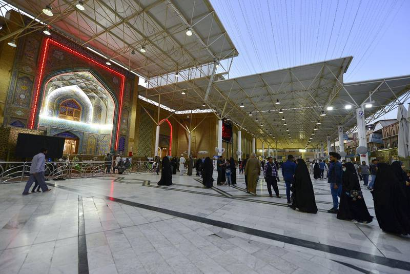 Visitors walk by at the Imam Ali shrine, in the holy Iraqi central city of Najaf where the first case of novel coronavirus infection in the country was confirmed, on March 10, 2020. (Photo by Haidar HAMDANI / AFP)