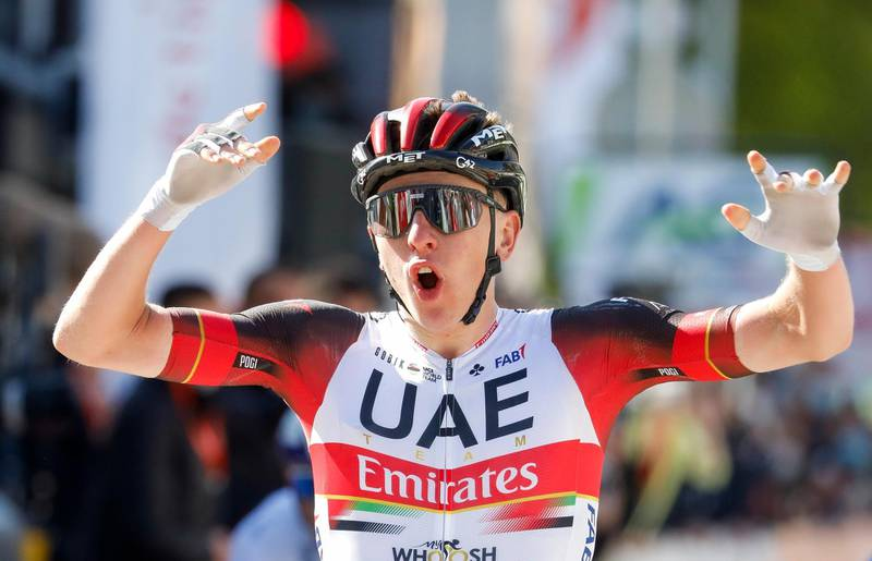 epa09158839 Slovenian rider Tadej Pogacar of the UAE Emirates team celebrates as he crosses the finish line to win the 107th edition of the Liege-Bastogne-Liege one day cycling race in Liege, Belgium, 25 April 2021.  EPA/JULIEN WARNAND