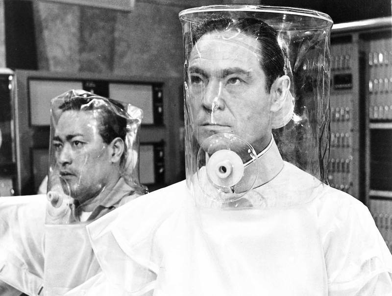 Anthony Chinn and Joseph Wiseman wearing decontamination suits in a scene from the film 'Doctor No', 1962. Courtesy United Artists