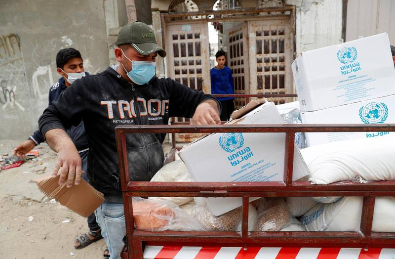 Palestinian workers distribute food supplies from the United Nations Relief and Works Agency (UNRWA) to a house in the Sheikh Redwan neighborhood of Gaza City, Tuesday, March 31, 2020. The United Nations has resumed food deliveries to thousands of impoverished families in the Gaza Strip after a three-week delay caused by fears of the coronavirus. (AP Photo/Adel Hana)