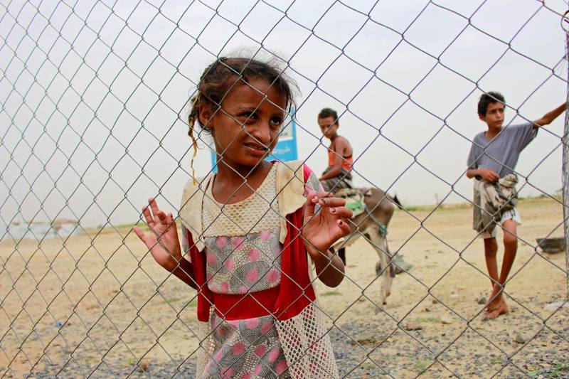 A girl looks through the fence of a closed clinic at a camp for internally displaced people near Abs of Hajjah province, Yemen August 19, 2020. Picture taken August 19, 2020. REUTERS/Eissa Alragehi NO RESALES. NO ARCHIVES.