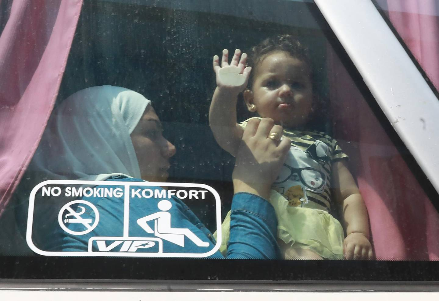 Syrian refugee Umm Luay, 30, sits with her child inside a bus on September 17, 2018  she return with her family to Syrian after living as refugees in Lebanon for years. In 2012, Rawad Kurdi and his 35 relatives were forced to flee their hometown of Babila southeast of Damascus after fighting broke out between rebels and government forces.  They came to Lebanon. Three years later, some of the elderly family members including Rawad's father Ahmad returned to Syria, and more have hit the road home since.   / AFP / ANWAR AMRO