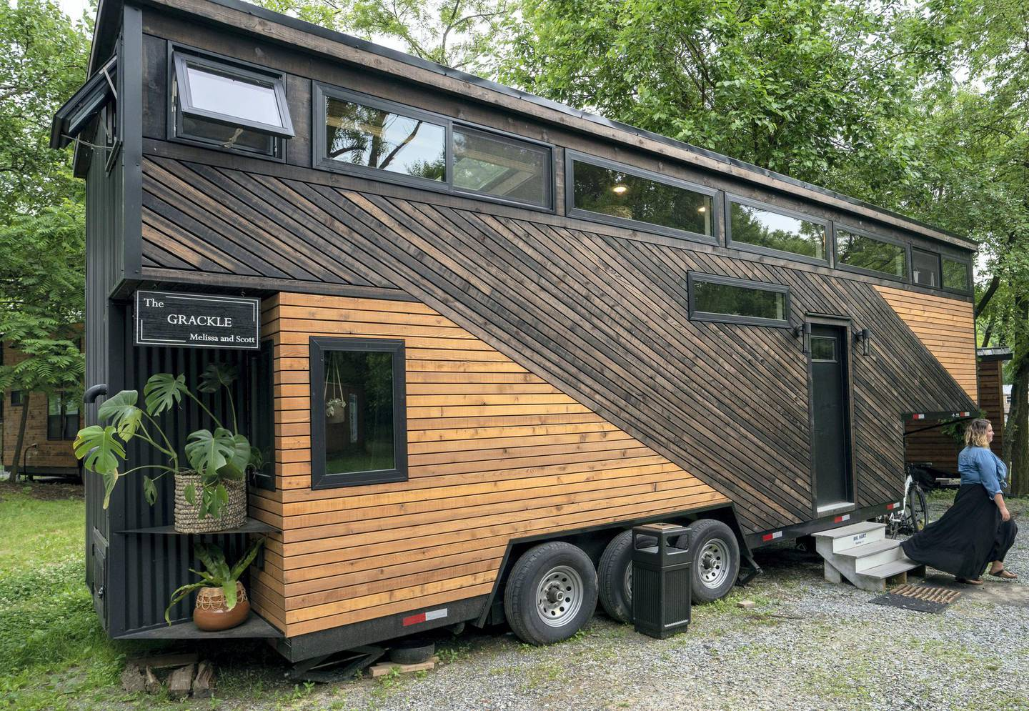 Melissa Meshey walks out of her tiny home called Grackle, built at Liberation Tiny Homes, on June 5, 2019 in Elizabethtown, Pennsylvania. - In a country where bigger is nearly always better -- think supersize fries, giant cars and 10-gallon hats -- more and more Americans are downsizing their living quarters.  Welcome to the world of tiny homes, most of them less than 430 square feet (40 square meters), which savvy buyers are snapping up for their minimalist appeal and much smaller carbon footprints. (Photo by Don Emmert / AFP)