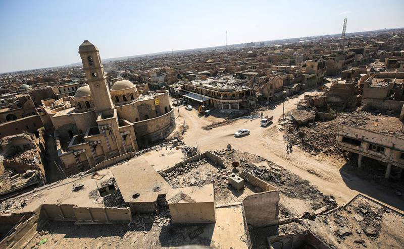"""(FILES) This file photo taken on March 14, 2018 shows a view of destruction surrounding the Roman Catholic Church of Our Lady of the Hour (L) in the old city of Mosul, eight months after it was retaken by Iraqi government forces from the control of Islamic State (IS) group fighters. An exhibition opens at the Institute of the Arab World (IMA) in Paris showing the """"millennia cities"""" resuscitated by the miracle of 3D, from Mosul to Aleppo. / AFP / AHMAD AL-RUBAYE"""