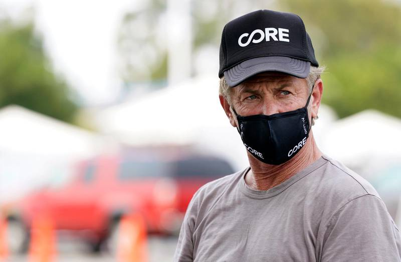 Actor Sean Penn, founder of Community Organized Relief Effort (CORE), sits for an interview at a CORE coronavirus testing site at Crenshaw Christian Center, Friday, Aug. 21, 2020, in Los Angeles. Penn says his organization CORE has made some strides against the coronavirus and he's keeping its mission going by expanding testing and other relief services. (AP Photo/Chris Pizzello)