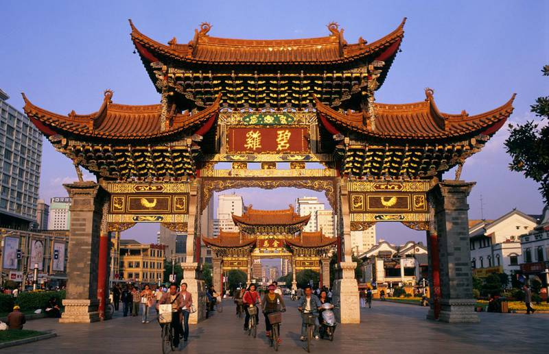 Kunming, China --- Pedestrians and Cyclists Under the Jinma Biji Archway --- Image by © Franck Guiziou/Hemis/Corbis