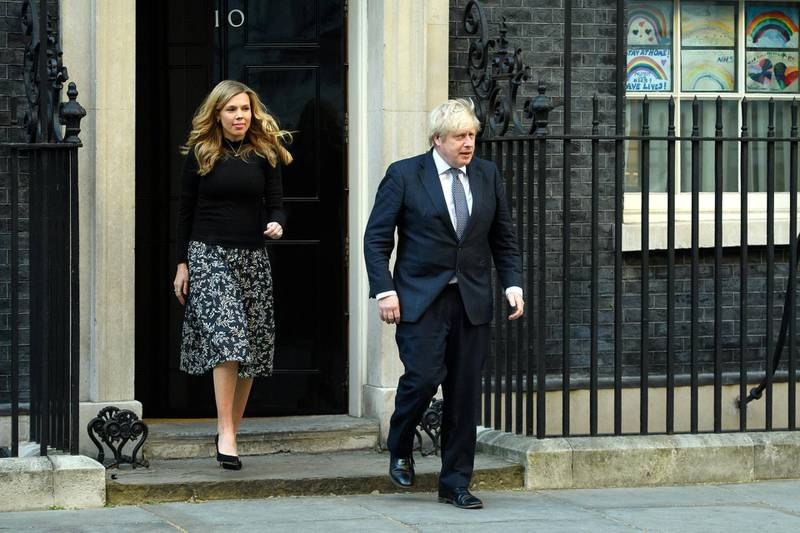 """LONDON, UNITED KINGDOM - MAY 14: Britain's Prime Minister Boris Johnson and his partner Carrie Symonds stand outside the door of number 10 Downing Street as they thank the key workers who are working during the current lockdown on May 14, 2020 in London, United Kingdom. Following the success of  the """"Clap for Our Carers"""" campaign, members of the public are being encouraged to applaud NHS staff and other key workers from their homes at 8pm every Thursday. The Coronavirus (COVID-19) pandemic has infected over 4 million people across the world, claiming at least  33,614 lives in the U.K. (Photo by Leon Neal/Getty Images)"""