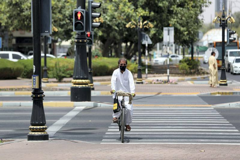 Al Ain, United Arab Emirates - Reporter: N/A: A man wearing a facemask rides his bike across the street in Al Ain. Thursday, April 9th, 2020. Al Ain. Chris Whiteoak / The National