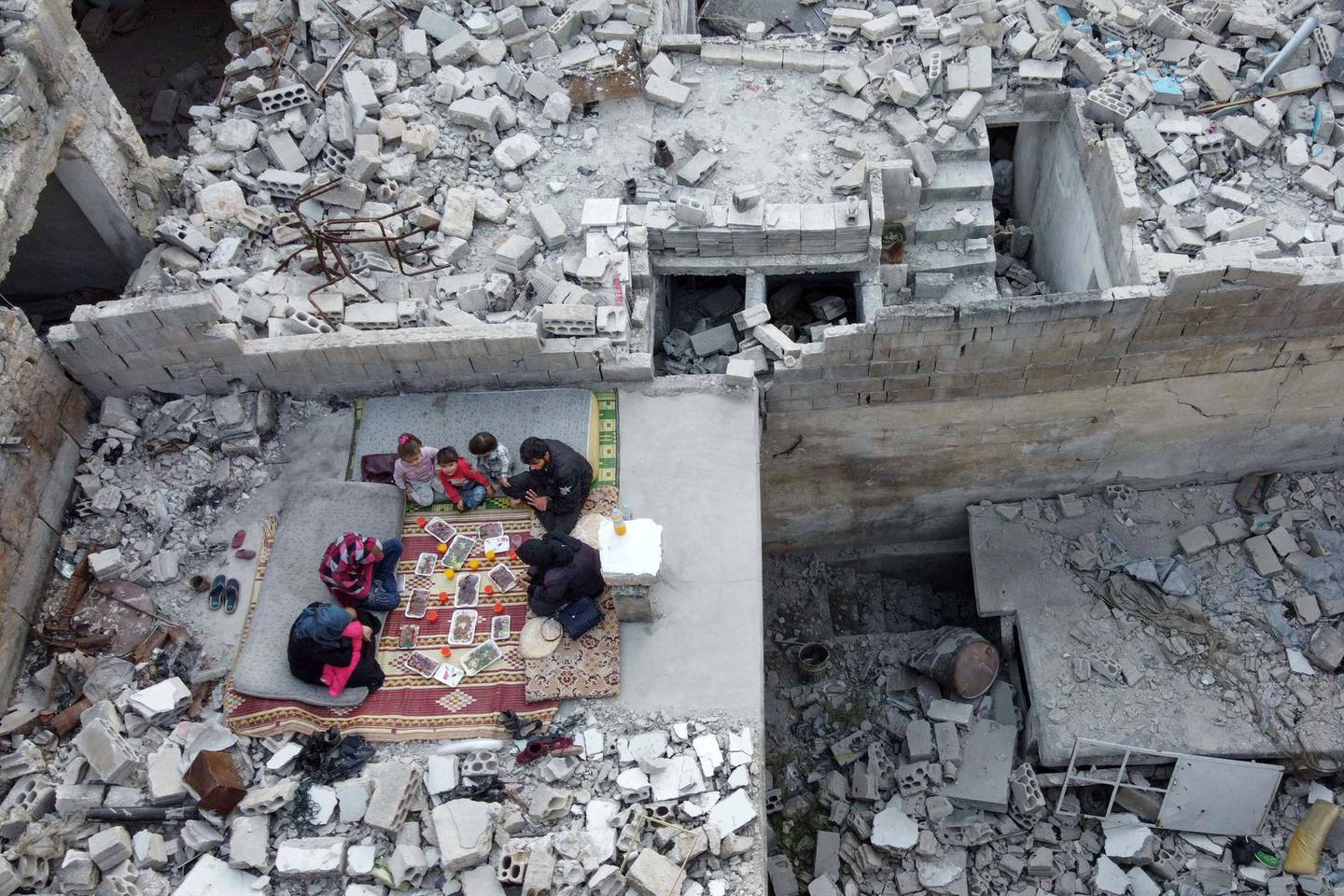 """This picture taken on May 4, 2020 during the Muslim holy fasting month of Ramadan shows an aerial view of members of the displaced Syrian family of Tariq Abu Ziad, from the town of Ariha in the southern countryside of the Idlib province, breaking their fast together for the sunset """"iftar"""" meal, in the midst of the rubble of their destroyed home upon their return to the town after fleeing during the previous military assault on the town by Syrian government forces and their allies.  / AFP / Aaref WATAD"""