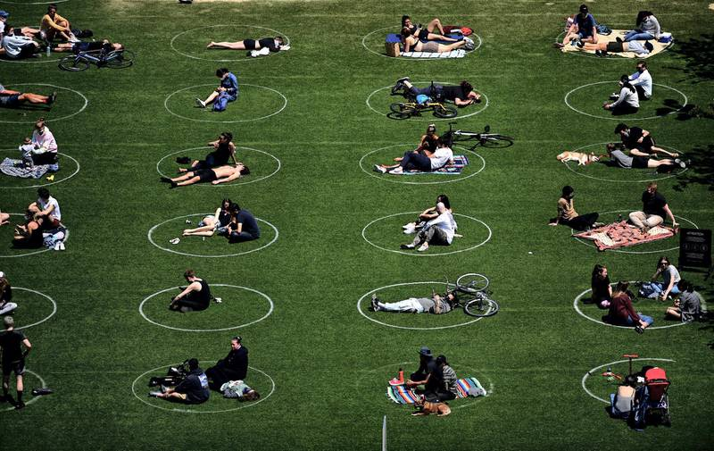 People are seen practising social distancing in white circles in Domino Park, during the Covid-19 pandemic on May 17, 2020 the in Brooklyn borough of New York City. (Photo by Johannes EISELE / AFP)