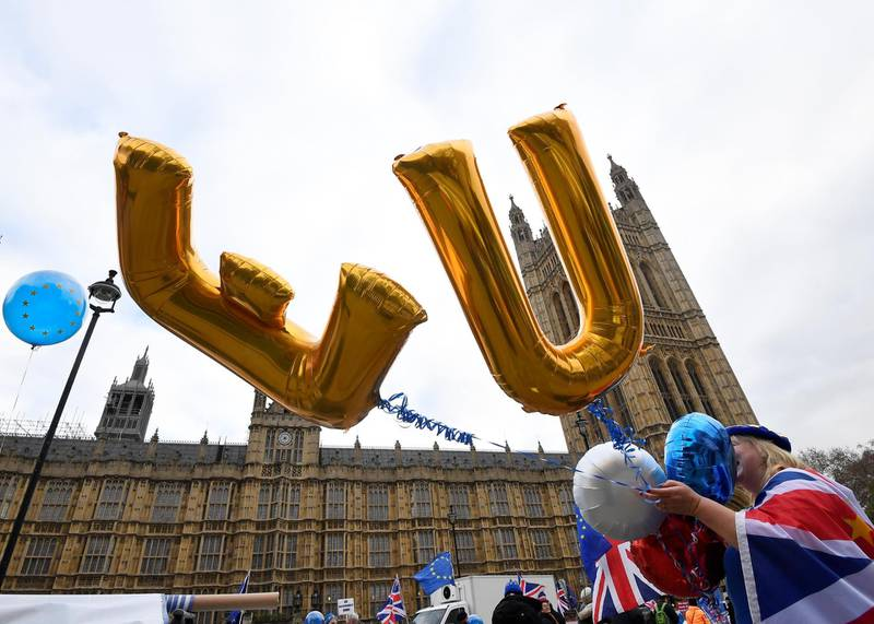 An anti-Brexit protester holds balloons opposite the Houses of Parliament in London, Britain, December 10, 2018. REUTERS/Toby Melville