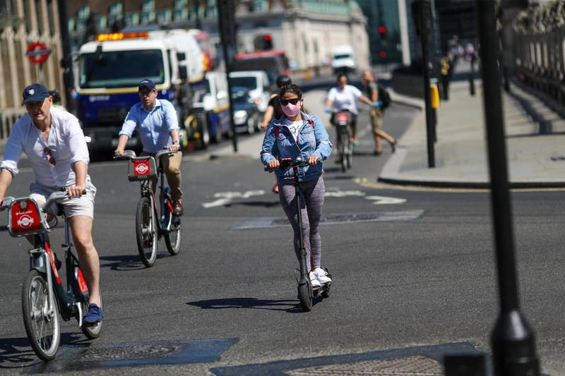 Cyclists and an electric scooter rider navigate a junction in London, U.K., on Thursday, May 21, 2020. The government in London is trying to reboot the economy while also extending a stay-at-home pay program. Photographer: Simon Dawson/Bloomberg via Getty Images