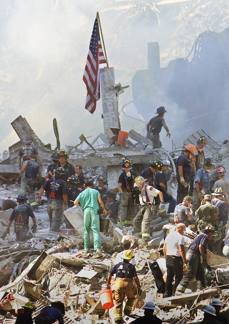 An American flag is posted in the rubble of the World Trade Center 13 September 2001 in New York. The search for survivors and the recovery of the victims continues since the 11 September terrorist attack. AFP PHOTO/Beth A. KEISER (Photo by BETH A. KEISER / AP POOL / AFP)