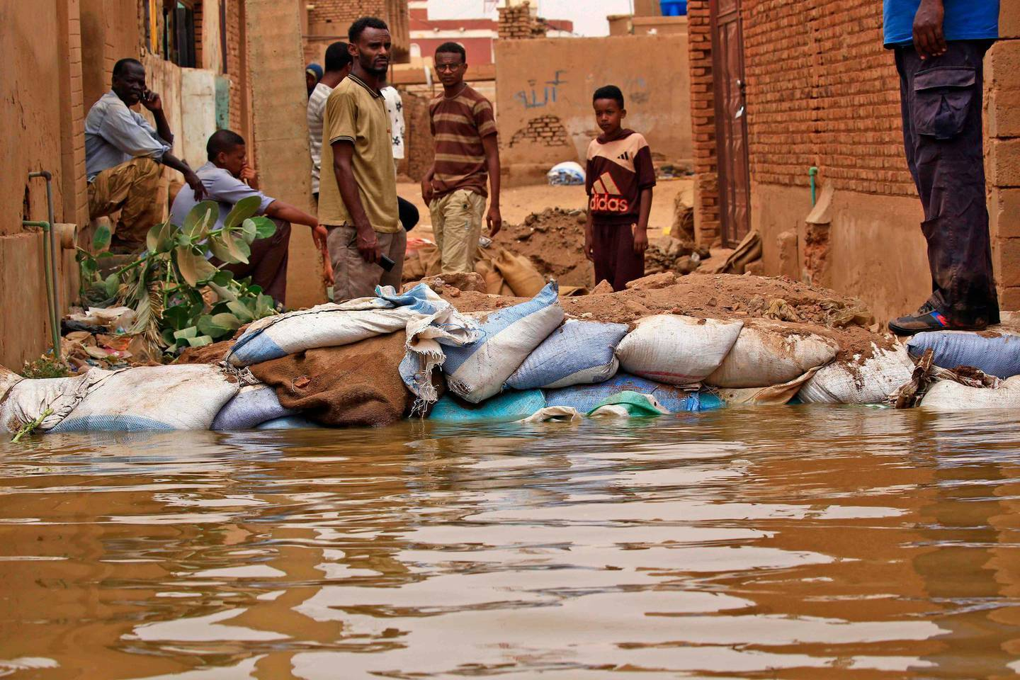 TOPSHOT - Sudanese stand amidst flood waters in Tuti island, where the Blue and White Nile merge in the Sudanese capital Khartoum, on September 3, 2020.  / AFP / ASHRAF SHAZLY