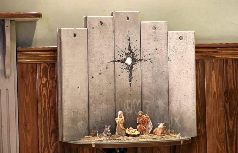 epa08086584 A view of a new artwork by elusive British graffiti artist Banksy depicting the nativity scene dubbed 'scar of Bethlehem', displayed in the Walled Off hotel, in the West Bank city of Bethlehem, 22 December 2019.  EPA-EFE/ABED AL HASHLAMOUN *** Local Caption *** 55725073