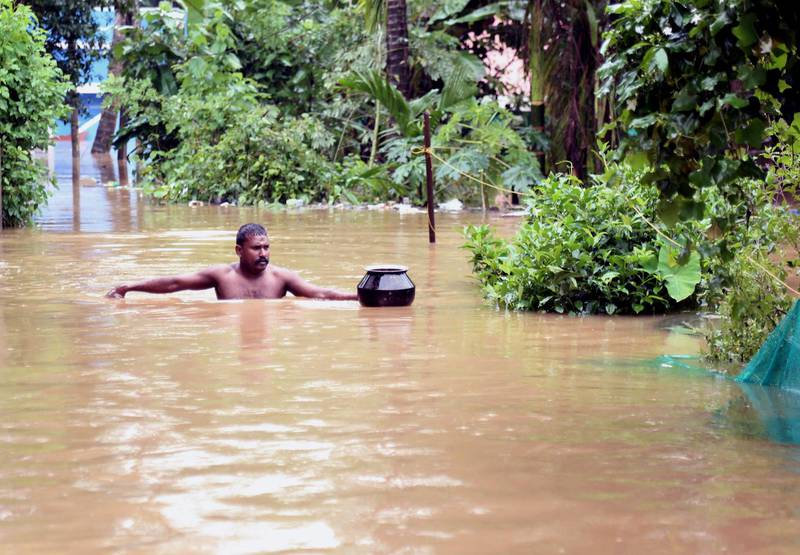 epa07763640 An Indian man wades through a flooded street in Kochi, Kerala, India, 09 August 2019. According to news reports, the operation of the Cochin International Airport has been stopped till 11 August after Heavy rains saw water levels rise in the Periyar river, near Cochin airport.  EPA/PRAKASH ELAMAKKARA