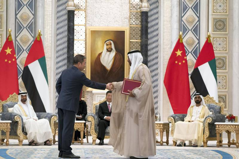 ABU DHABI, UNITED ARAB EMIRATES - July 20, 2018:  HE Ahmed Ali Al Sayegh, Chairman of Abu Dhabi Global Market (R), exchanges an MOU with a member of the Chinese delegation, at the Presidential Palace. Witnessed by HH Sheikh Mohamed bin Rashid Al Maktoum, Vice-President, Prime Minister of the UAE, Ruler of Dubai and Minister of Defence (back R), HE Xi Jinping, President of China (back C) and HH Sheikh Mohamed bin Zayed Al Nahyan, Crown Prince of Abu Dhabi and Deputy Supreme Commander of the UAE Armed Forces (back L).  ( Mohamed Al Hammadi / Crown Prince Court - Abu Dhabi ) ---