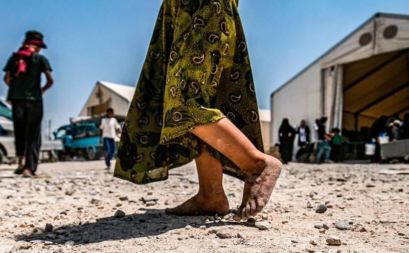 (FILES) In this file photograph taken on July 22, 2019, a young child walks barefoot at al-Hol camp for displaced people, in al-Hasakeh governorate, north-eastern Syria, as people collect UN-provided humanitarian aid packages. The government said June 22, 2020, that it had brought home 10 French children of jihadist fighters overnight from a refugee camp in Syria, the latest in a piecemeal repatriation process since the Islamic State group was ousted from its Syrian base in March 2019. / AFP / Delil souleiman