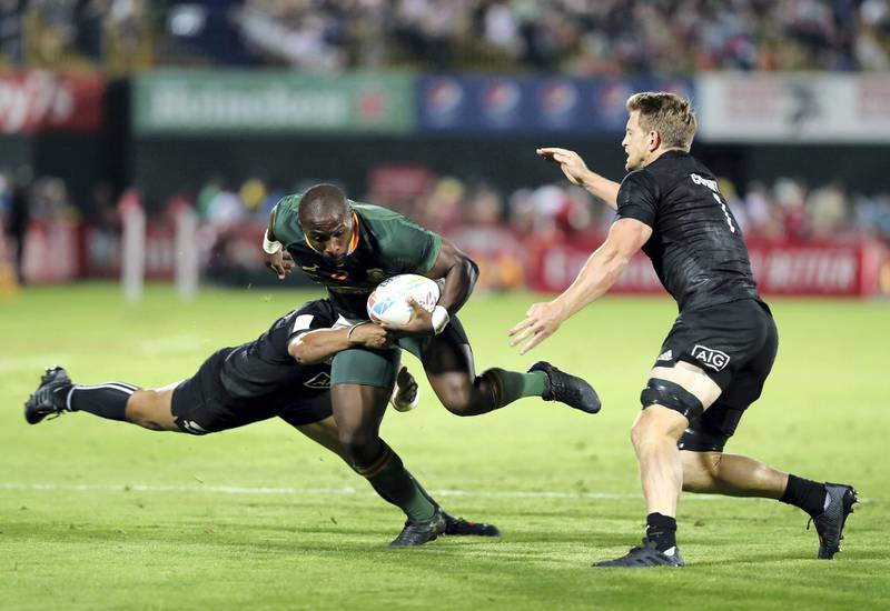 Dubai, United Arab Emirates - December 07, 2019: Siviwe Soyizwapi of South Africa is tackled by Ngarohi McGarvey-Black of New Zealand during the game between New Zealand and South Africa in the mens final at the HSBC rugby sevens series 2020. Saturday, December 7th, 2019. The Sevens, Dubai. Chris Whiteoak / The National