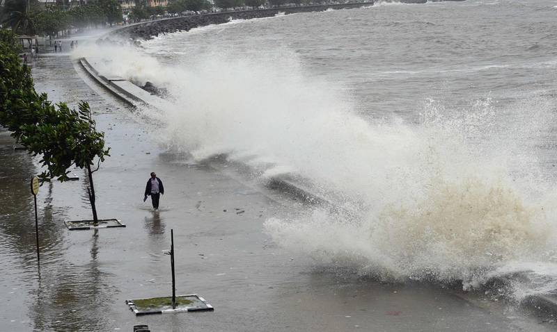 A man walks past as waves strike the promenade during high-tide in Mumbai on July 16, 2018.   / AFP / Indranil MUKHERJEE