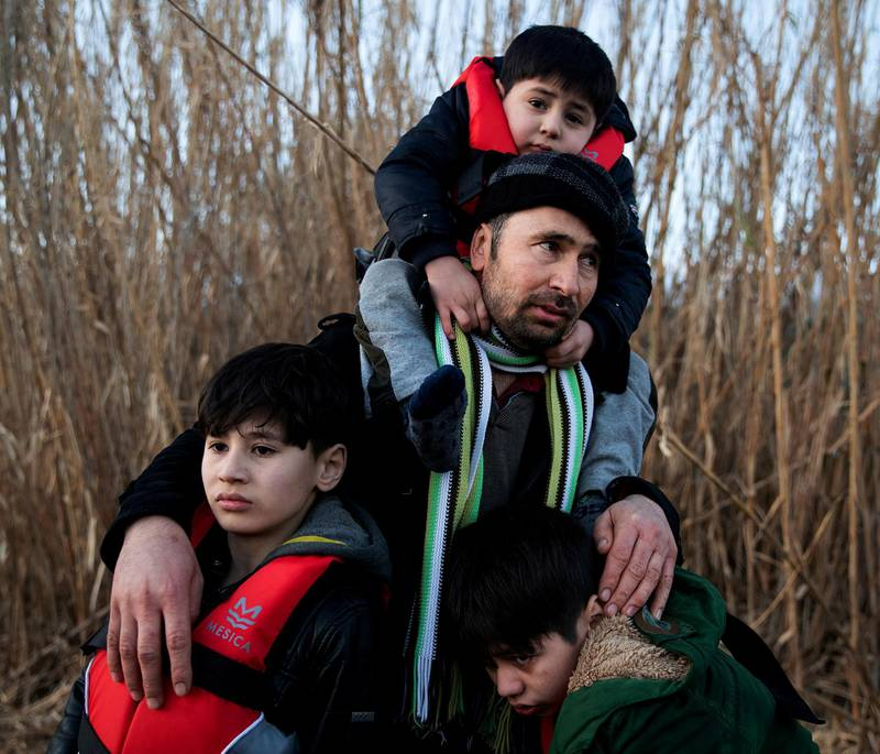 A man holds his three sons as migrants from Afghanistan arrive on a dinghy on a beach near the village of Skala Sikamias, after crossing part of the Aegean Sea from Turkey to the island of Lesbos, Greece, March 2, 2020. REUTERS/Alkis Konstantinidis     TPX IMAGES OF THE DAY