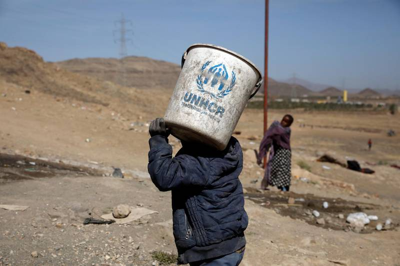 epa09045435 A displaced Yemeni boy carries a UNHCR bucket at a camp for Internally Displaced Persons (IDPs) on the outskirts of Sana'a, Yemen, 01 March 2021. The five-year al-Azraqeen IDPs camp in the northern outskirts of Sana'a was rebuilt by the Norwegian Refugee Council in 2020 with orange wooden huts in place of the tents and small stone huts that the displaced people were using as their refuges. The camp hosts more than 60 displaced families, who were forcibly displaced by the escalating fighting in the northern areas of Yemen. The prolonged conflict has plunged Yemen into the world's largest humanitarian crisis with an estimated 80 percent of Yemen's 29 million-population are in need of humanitarian assistance, and led to the displacement of more than three million people.  EPA/YAHYA ARHAB