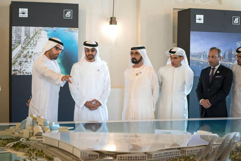 DUBAI, UNITED ARAB EMIRATES - March 20, 2018: HH Sheikh Mohamed bin Zayed Al Nahyan Crown Prince of Abu Dhabi Deputy Supreme Commander of the UAE Armed Forces (2nd L) and HH Sheikh Mohamed bin Rashid Al Maktoum, Vice-President, Prime Minister of the  UAE, Ruler of Dubai and Minister of Defence (3rd L), view a plan of Saadiyat Island before the signing of a joint venture agreement between Aldar and Emaar. Seen with HE Mohamed Khalifa Al Mubarak, Chairman of the Department of Culture and Tourism and Abu Dhabi Executive Council Member (L) and HE Mohamed Al Abbar, Founder and Chairman of Emaar Properties and Board Member of Eagle Hills (4th L), in Shindagha Heritage District.   ( Mohamed Al Hammadi / Crown Prince Court - Abu Dhabi ) ---