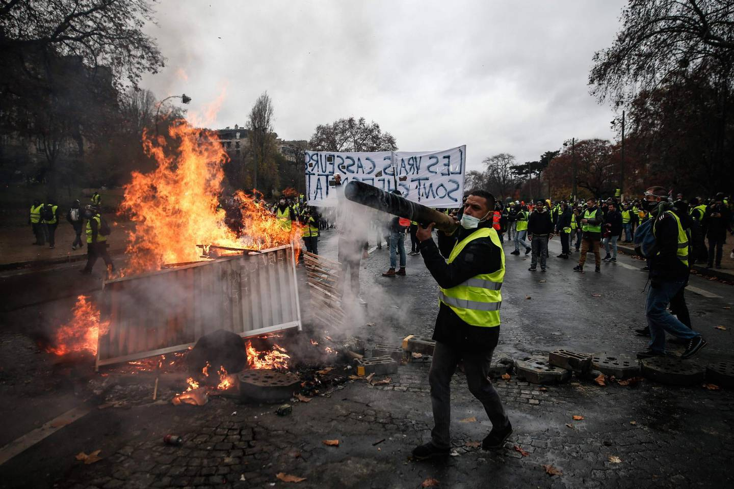TOPSHOT - Protesters build a barricade during a protest of Yellow vests (Gilets jaunes) against rising oil prices and living costs, on December 1, 2018 in Paris.   / AFP / Abdulmonam EASSA