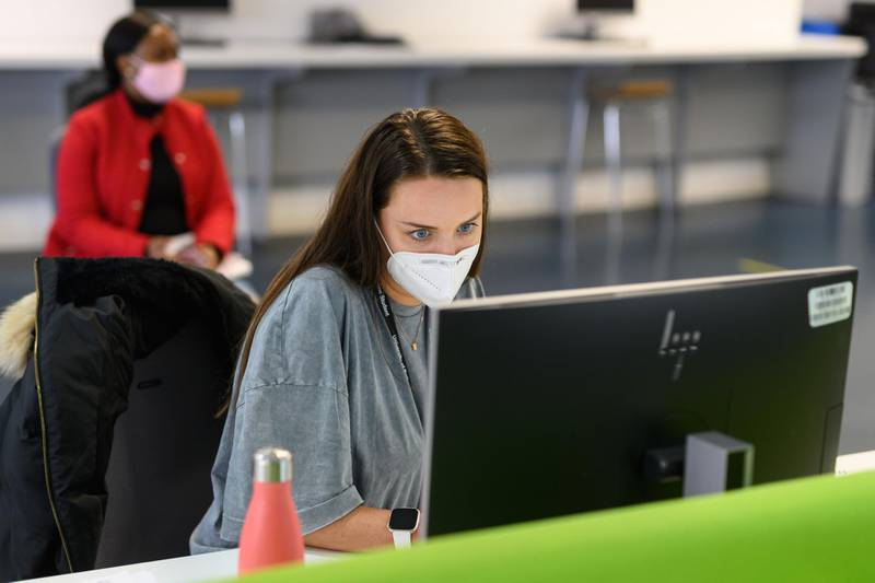 Students, wearing face masks to help mitigate the spread of the novel coronavirus COVID-19, work on computers in the Social Learning Zone at the University of Bolton, in Bolton, northern England on October 7, 2020.     The University of Bolton has introduced numerous Covid-safety measures across its campus including: airport-style temperature scanners, socially distanced seating, perspex screens and visors for lecturers, a bicycle loan scheme for students, one-way routes throughout campus buildings and additional online resources for student learning. Hundreds of thousands of students have begun a new academic year at universities across the UK. / AFP / OLI SCARFF
