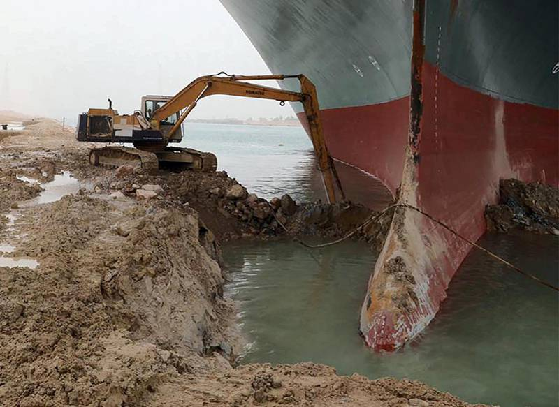 """A handout picture released by the Suez Canal Authority on March 25, 2021 shows the Taiwan-owned MV Ever Given (Evergreen), a 400-metre- (1,300-foot-)long and 59-metre wide vessel, lodged sideways and impeding all traffic across the waterway of Egypt's Suez Canal. Egypt's Suez Canal Authority said it was """"temporarily suspending navigation"""" until refloating of the MV Ever Given ship was completed on one of the busiest maritime trade routes. / AFP / Suez CANAL / - / == RESTRICTED TO EDITORIAL USE - MANDATORY CREDIT """"AFP PHOTO / HO / Suez Canal"""" - NO MARKETING NO ADVERTISING CAMPAIGNS - DISTRIBUTED AS A SERVICE TO CLIENTS =="""