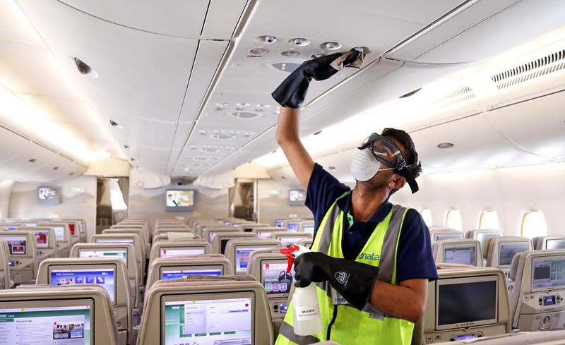 """A handout image provided by Emirates airlines on March 8, 2020 in Dubai shows a member of the cleaning staff disinfecting air vents aboard an Emirates Airbus A380-800 aircraft for sterilisation efforts amidst efforts against COVID-19 coronavirus disease.  - === RESTRICTED TO EDITORIAL USE - MANDATORY CREDIT """"AFP PHOTO / HO / EMIRATES"""" - NO MARKETING NO ADVERTISING CAMPAIGNS - DISTRIBUTED AS A SERVICE TO CLIENTS ===  / AFP / Emirates Airlines / - / === RESTRICTED TO EDITORIAL USE - MANDATORY CREDIT """"AFP PHOTO / HO / EMIRATES"""" - NO MARKETING NO ADVERTISING CAMPAIGNS - DISTRIBUTED AS A SERVICE TO CLIENTS ==="""