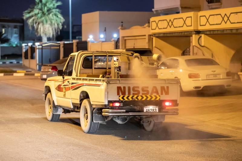 SHARJAH, UNITED ARAB EMIRATES. 26 MARCH 2020. Sharjah Municipal staff spray and disinfect the sidewalk along the Al Muntazah Str area of Sharjah near the Ajman border. (Photo: Antonie Robertson/The National) Journalist: None. Section: National.