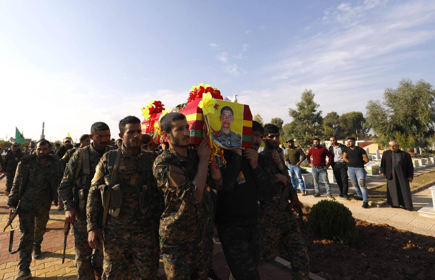 CORRECTION / Fighters from the Syrian Democratic Forces (SDF), carry the coffin of a fellow fighter  the funeral of a fellow fighter, killed during a military mission, in the Kurdish-controlled city of Qamishly in northeastern Syria, on November 11, 2018.   The Kurdish-led force SDF, joint Arab-Kurdish units backed by the US-led anti-jihadist coalition said today that it was resuming its offensive against the Islamic State (IS) group in eastern Syria. They had announced a suspension to their operation on October 31 after Turkey shelled Kurdish militia posts in northern Syria.  / AFP / Delil SOULEIMAN