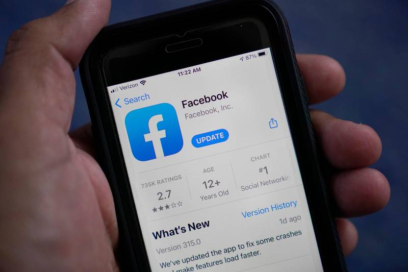 """The Facebook app is shown on a smart phone, Friday, April 23, 2021, in Surfside, Fla.  Facebook says, Thursday, May 27,  it will no longer remove claims that COVID-19 is man-made or manufactured from its apps. The change comes """"in light of ongoing investigations into the origin of COVID-19 and in consultation with public health experts,"""" Facebook said.  .(AP Photo/Wilfredo Lee)"""