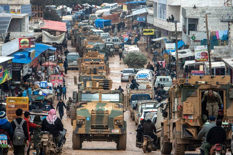 """IDLIB, SYRIA - FEBRUARY 22: Turkish Military's armoured vehicles that crossed to Syria drive pass in a road in village of Aaqrabate on February 22, 2020 in Idlib, Syria. Turkey's President Recep Tayyip Erdogan in a speech Tuesday threatened, """"imminent operations in Syria's Idlib if Damascus fails to withdraw behind Turkish positions"""" The threat comes after Syria's government and its ally Russia rejected demands to pull back to ceasefire lines agreed upon in the 2018 Sochi accord. More than 900,000 civilians have been displaced by fighting in or around Idlib since December 1. Idlib is the last rebel stronghold of fighters trying to overthrow Syrian President Bashar al-Assad and in the past years has become the last safe haven for civilians displaced by fighting in other areas of Syria, its population has doubled to close to three million people, many of whom are now fleeing the government offensive towards overcrowded camps close to the Turkish border amid freezing conditions, creating a humanitarian disaster. (Photo by Burak Kara/Getty Images)"""