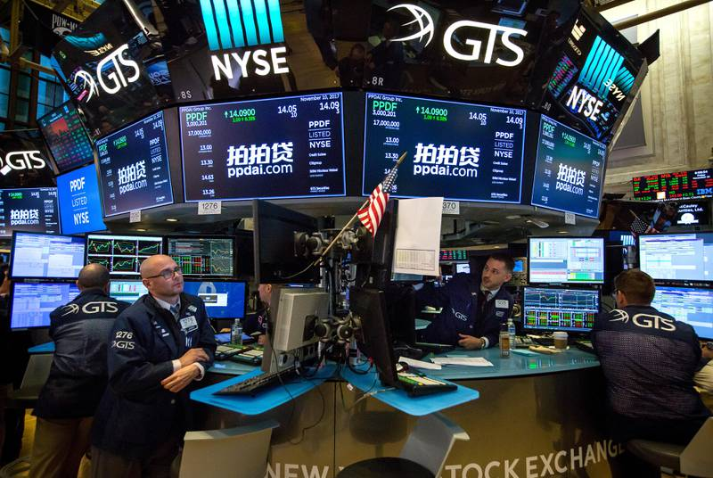 Traders work beneath monitors displaying PPDAI Group Inc. signage on the floor of the New York Stock Exchange (NYSE) in New York, U.S., on Friday, Nov. 10, 2017. Treasuries fell for a third day and U.S. stocks limped to the end of a week that saw a bout ofvolatilityreturn to global financial markets. Photographer: Michael Nagle/Bloomberg
