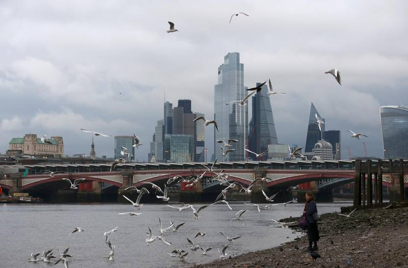 FILE PHOTO: A woman feeds birds on the bank of the river Thames with London's financial district seen in the background, amid the coronavirus disease (COVID-19) in London, Britain, November 25, 2020. REUTERS/Simon Dawson/File Photo