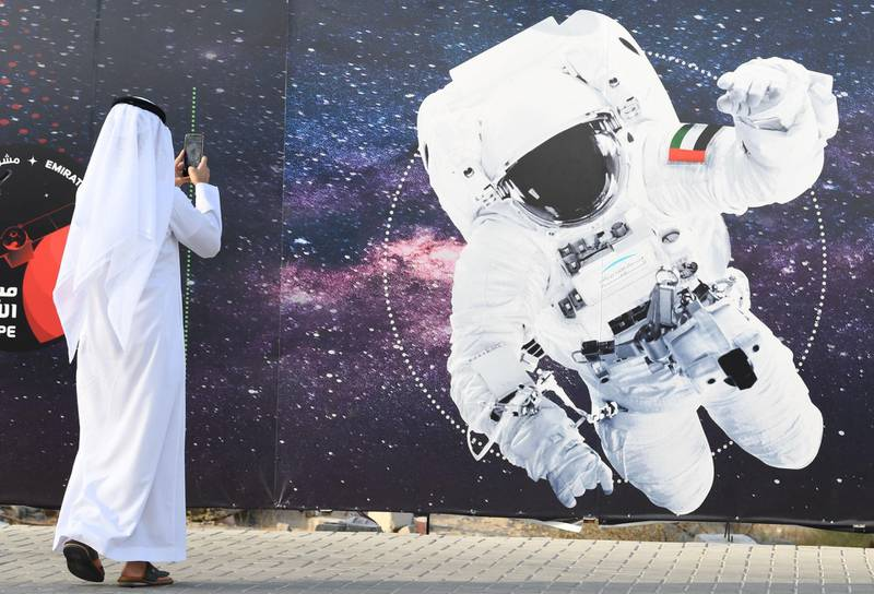 (FILES) In this file photo taken on September 25, 2019 (FILES) In this file photo taken on September 25, 2019 a man takes a picture of an illustration depicting an astronaut with the Emirati national flag outside Mohammed Bin Rashid Space Centre (MBRSC) in Dubai. The first Arab space mission to Mars, set for launch next month to study the Red Planet's atmosphere, is designed to inspire the region's youth and pave the way for scientific breakthroughs, officials said on June 9, 2020.  / AFP / KARIM  SAHIB