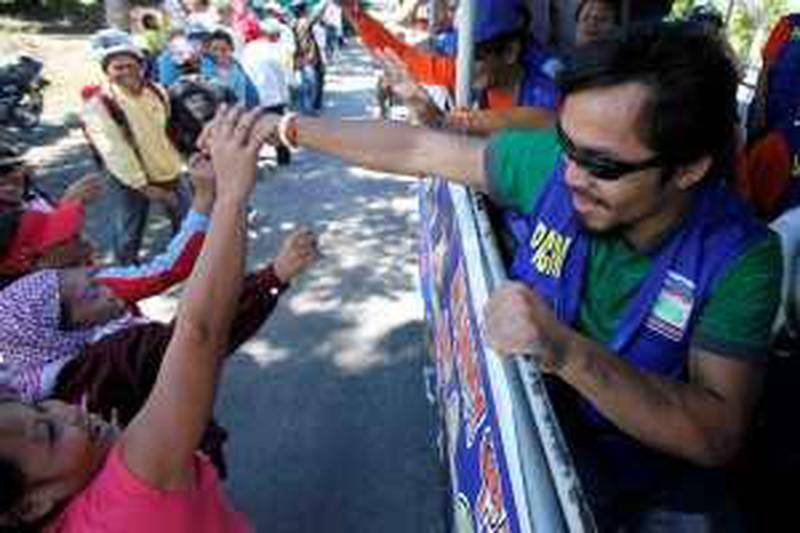 Filipino boxing great Manny Pacquiao, a candidate for Congressman at the seven-township Sarangani province, greets supporters as his campaign motorcade makes the rounds of townships on the second day of the official campaign period Saturday Mar.27, 2010 in Malungon township, Sarangani province in southern Philippines. Pacquiao, who made boxing history by winning seven championships in seven weight divisions and recently won a unanimous WBO Welterweight crown versus Joshua Clottey of Ghana, is now concentrating on another fight in the political arena as a candidate for congressman in Sarangani province in southern Philippines. (AP Photo/Bullit Marquez) *** Local Caption ***  XBM102_Philippines_Pacquiao_Election.jpg *** Local Caption ***  XBM102_Philippines_Pacquiao_Election.jpg