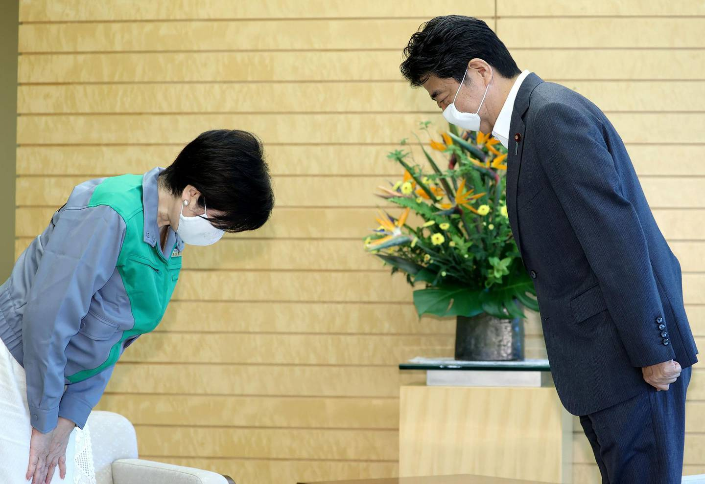 Japan's Prime Minister Shinzo Abe (R) and Tokyo governor Yuriko Koike (L) bow to greet each other during a meeting at the prime minister's official residence in Tokyo, on July 6, 2020. Tokyo governor Yuriko Koike declared victory on July 5, 2020 in the vote to elect the leader of one of the world's most populous cities and immediately vowed to step up the fight against a recent coronavirus resurgence. - Japan OUT  / AFP / JIJI PRESS / STR