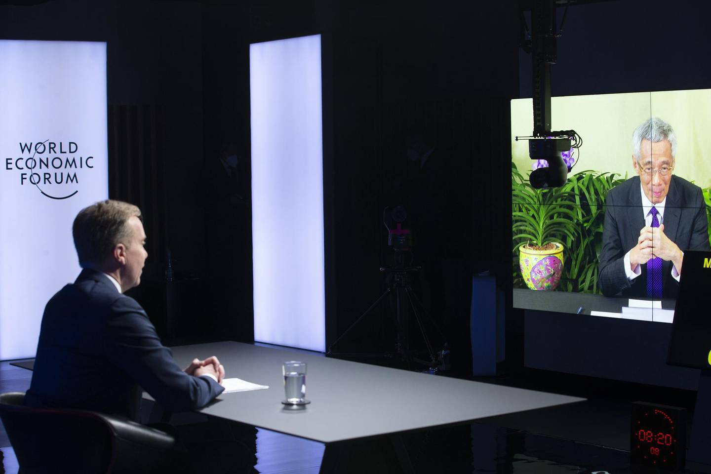 epa08972436 Norwegian Borge Brende (L), President and Member of the Managing Board of the World Economic Forum, WEF, looks on as Singapore's Prime Minister Lee Hsien Loong displayed in screens during a videoconference at the Davos Agenda, in Cologny, Switzerland, 29 January 2021. The Davos Agenda, held from 25 to 29 January 2021, is a online edition due to the coronavirus (COVID-19 disease) outbreak gather global leaders to shape the principles, policies and partnerships needed in this challenging new context.  EPA/SALVATORE DI NOLFI