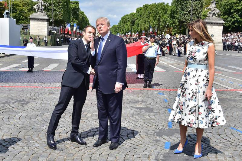(FILES) In this file photograph taken on July 14, 2017, French President Emmanuel Macron (L) gestures as he shakes hands with US President Donald Trump (C) next to US First Lady Melania Trump, during the annual Bastille Day military parade on the Champs-Elysees avenue in Paris. US President Trump has asked for a military parade to showcase US muscle and underscore his role as commander-in-chief, the White House said February 6, 2018. Trump, who has toyed with the idea of a parade in Washington since before being sworn in, has made the request to officers, who are looking for a date. / AFP PHOTO / POOL AND AFP PHOTO / CHRISTOPHE ARCHAMBAULT