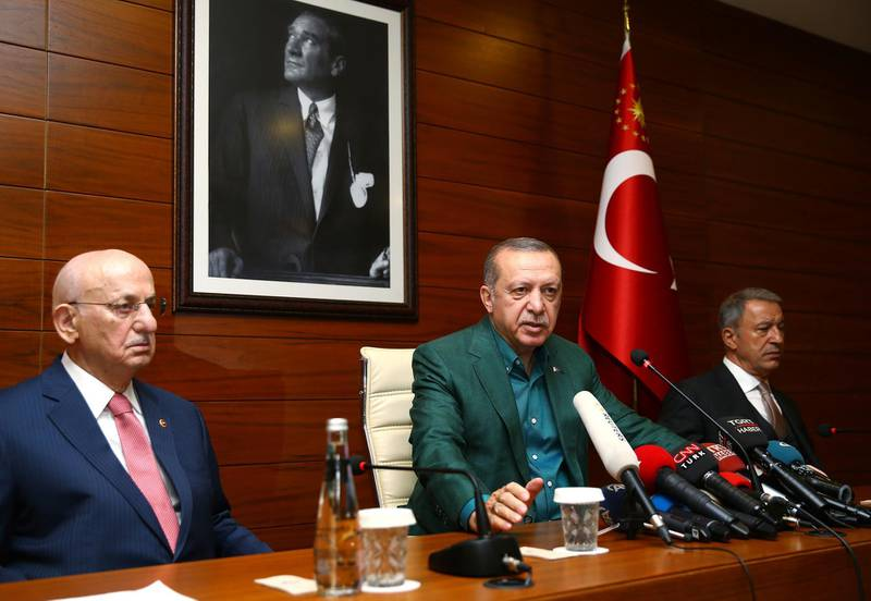 Turkey's President Recep Tayyip Erdogan, center, speaks to the media at Ataturk Airport before his departure for London for a two-day official visit, in Istanbul, Sunday, May 13, 2018. Parliament Speaker Ismail Kahraman, left, and Chief of Staff Gen. Hulusi Akar listen.(Presidential Press Service/Pool via AP)