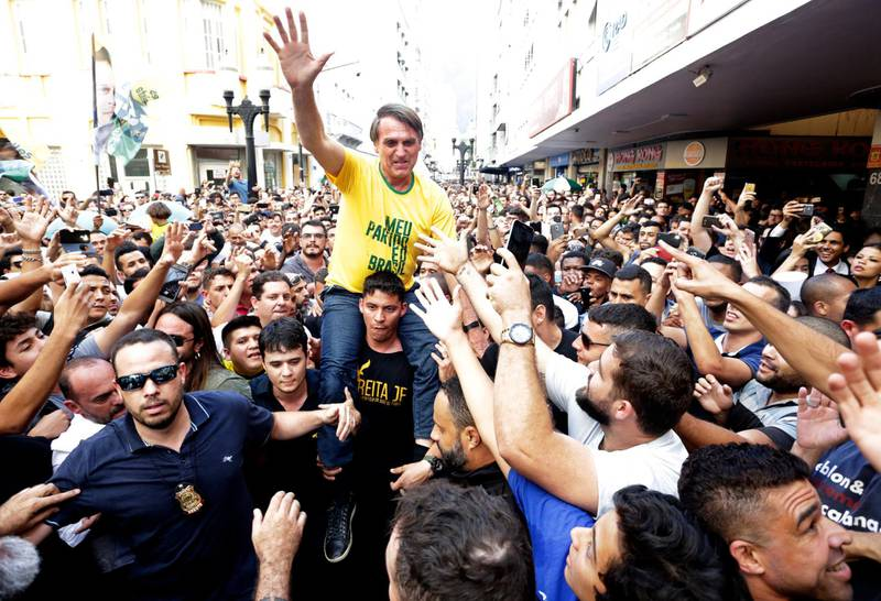Presidential candidate Jair Bolsonaro is taken on the shoulders of a supporter moments before being stabbed during a campaign rally in Juiz de Fora, Brazil, Thursday, Aug. 6, 2018. Bolsonaro's son said the injury is not life-threatening. (Antonio Scorza/Agencia O Globo via AP)