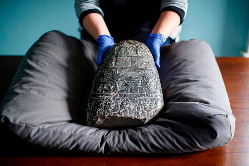 TOPSHOT - A gallery assistant poses with a Babylonian cuneiform kudurru (boundary stone) which was looted from Iraq on March 19, 2019 at the British museum in London. The kudurru which was seized at London's Heathrow airport in 2012 was handed over to representatives of the Iraq embassy today at the British museum. / AFP / Tolga Akmen